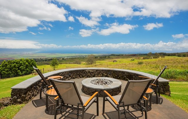 Luxury backyard fire pit surrounded by outdoor seating area and panoramic views