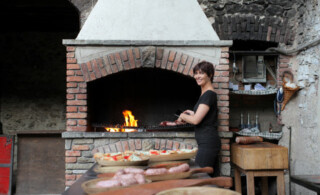 Woman grilling in front of an outdoor wood fireplace