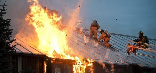 Fire fighters on roof of a home in flames