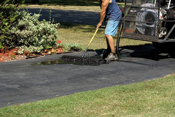 man adds sealer to his asphalt driveway