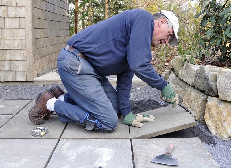 man installs stone paver patio