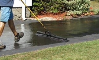 sealing an asphalt driveway with a brush