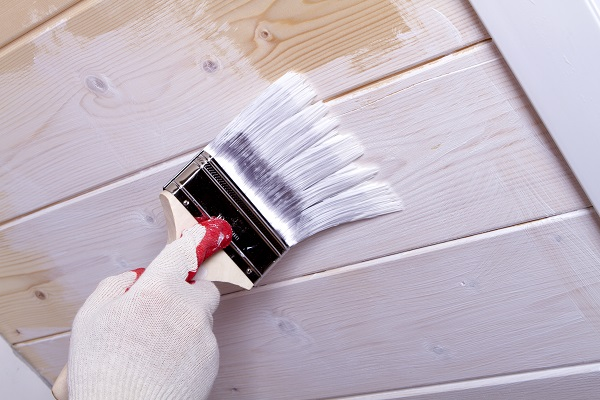 gloved hand paint wooden ceiling linings in white