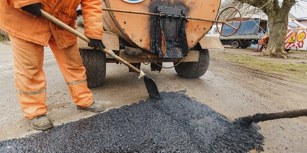 How to seal an asphalt or concrete driveway apply blacktop sealer working men in orange overalls repairing the road shovels fill asphalt road repair solutioingenieria Image collections