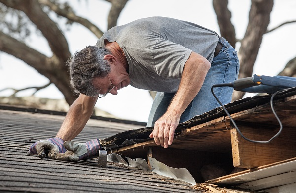 man inspects and repairs a roof