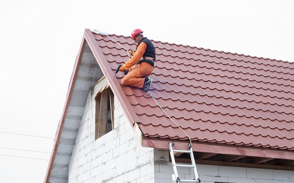 roofer repairing tile shingle roof