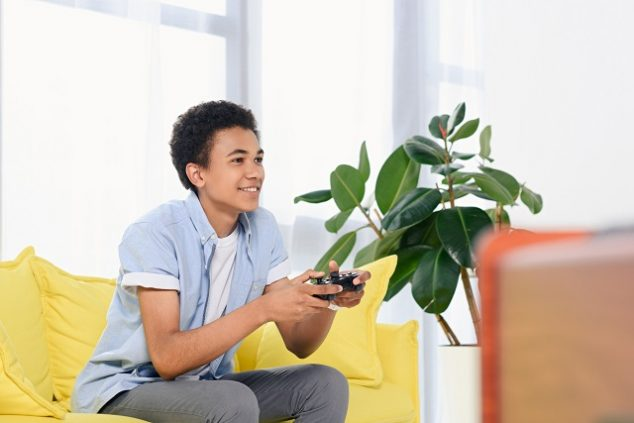 Teenager playing video games at home alone