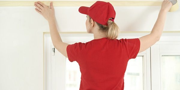 Woman painter worker protecting ceiling moulding with masking tape before painting at home improvement work
