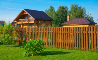wooden fence on green grass with a bush and two houses in background