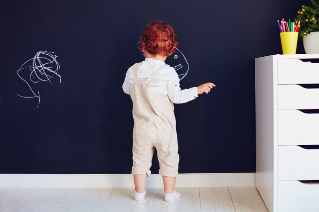 redhead boy drawing on the chalk wall at home