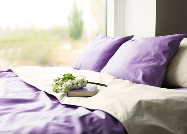 Lilac color accent in modern interior. Comfortable bed with book and bouquet in bedroom