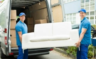 two movers with sofa loading it into a van