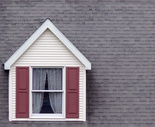 vinyl window on home with burgundy shutters