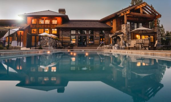 beautiful large home with pool at dusk with lights on