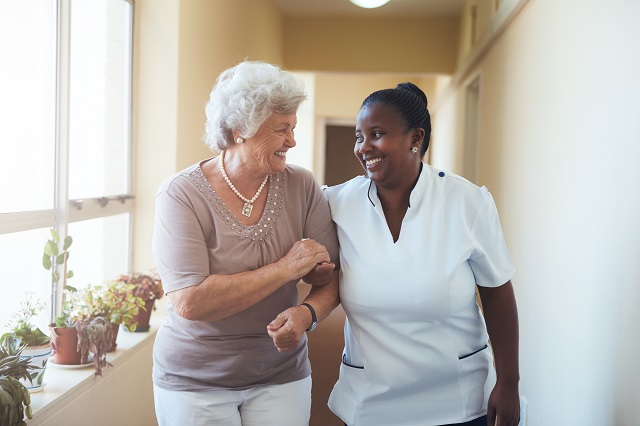 Smiling home caregiver and senior woman walking together