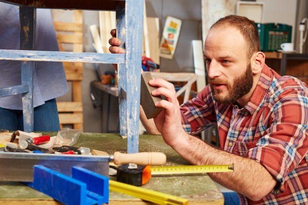 Handyman polishing wooden surface