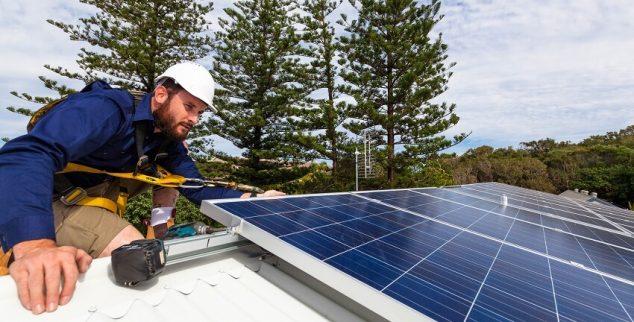 man installs solar panel on roof