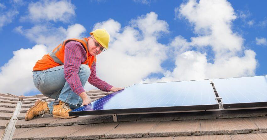 elder man installs solar panels on a home
