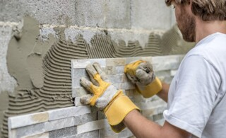 professional installs tile onto a wall