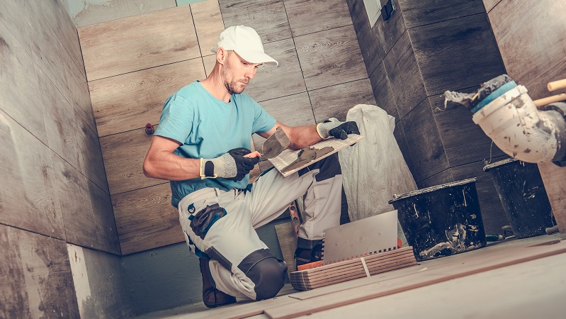 man applies tile during a bathroom remodel
