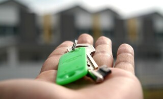 Hand holding keys in front of row of houses