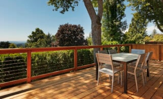 view of wood deck with patio furniture, fence, and green yard in background