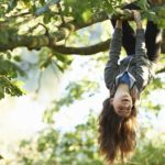 Young girl playing in tree, hanging upside down from branch