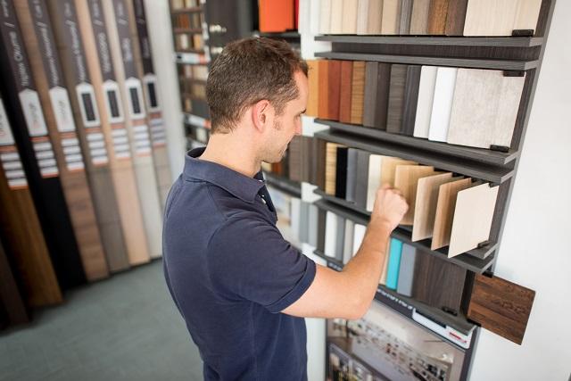 Man at a floor store looking at wood samples