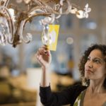 Woman Looking at Price Tag of Chandelier