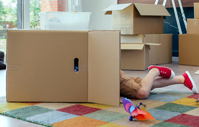 Child hiding or playing in moving box
