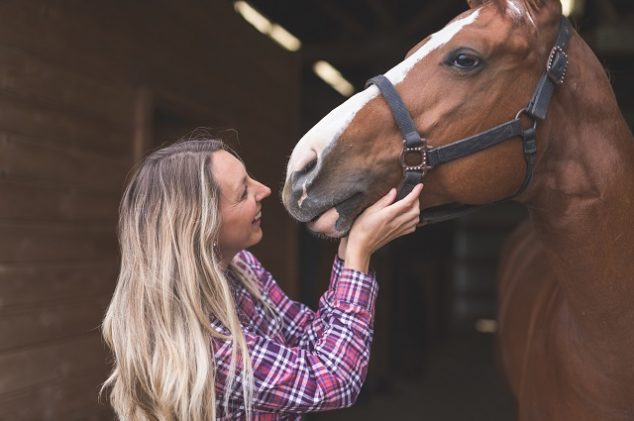 A woman and her horse in a barn
