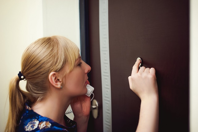 Woman anxiously looking through peephole on the phone