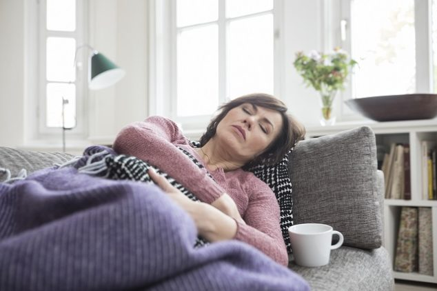 Woman who appears to be sick and resting on her couch