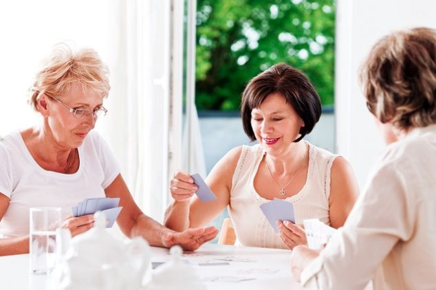 Three mature women playing cards together.