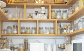 Woven baskets and food jars in pantry with built-in shelves