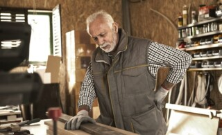 Mature carpenter experiencing back pain while checking wood plank in his workshop