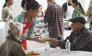 Volunteer helping the homeless by serving food at community kitchen