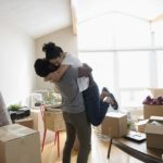 Couple hugging in new home, unpacking cardboard boxes