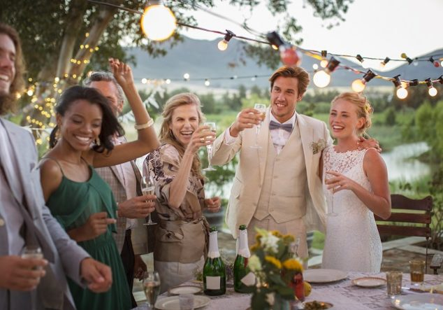Young couple and guests toasting with champagne during wedding reception in backyard