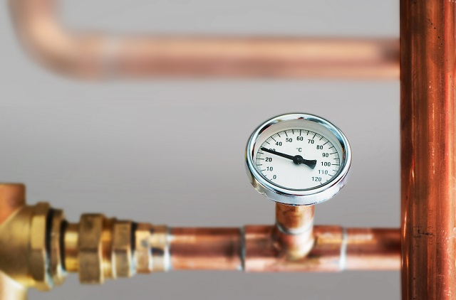 Heating system's cooper pipes with Thermometer on a copper pipe