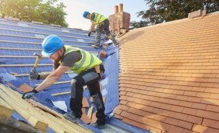 roofers nail down roof matting and tiles