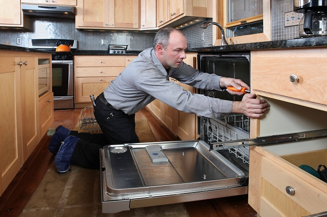 Worker installing energy efficient dishwasher in beautiful kitchen.