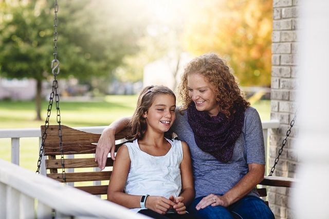 Aunt and niece sitting on a finished porch swing
