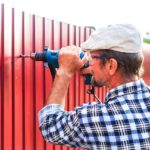 Man in plaid shirt and hat screws a vinyl fence board into a post