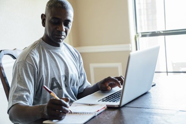Middle aged man in army shirt working on laptop at home