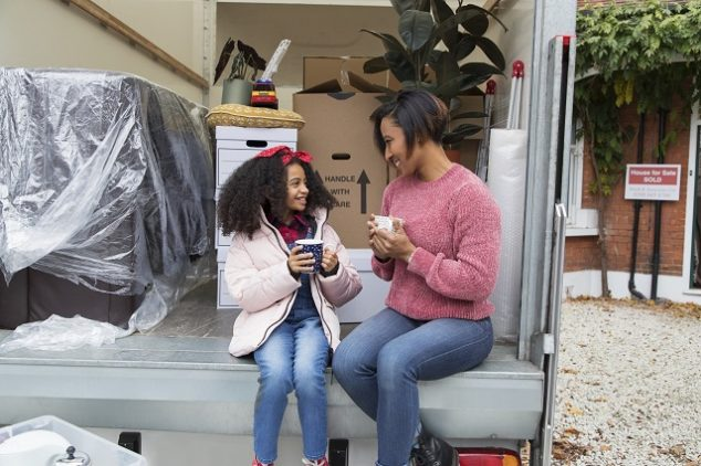 Mother and daughter drinking tea at back of moving van