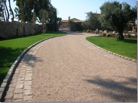 Long chip seal driveway leading to a house