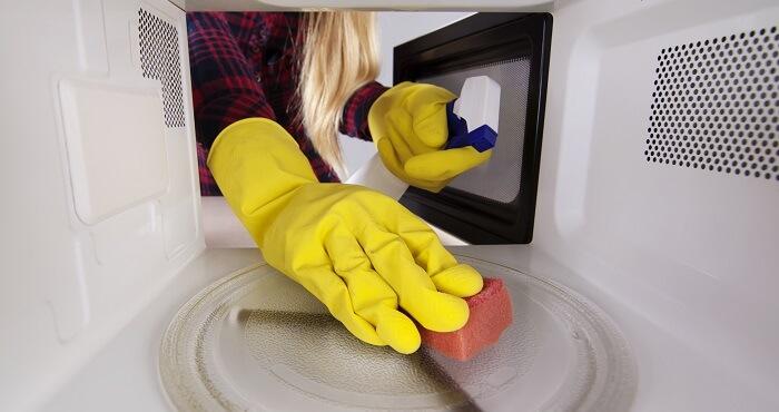 woman scrubs a microwave
