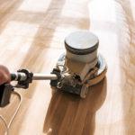 man buffer cleans laminate flooring