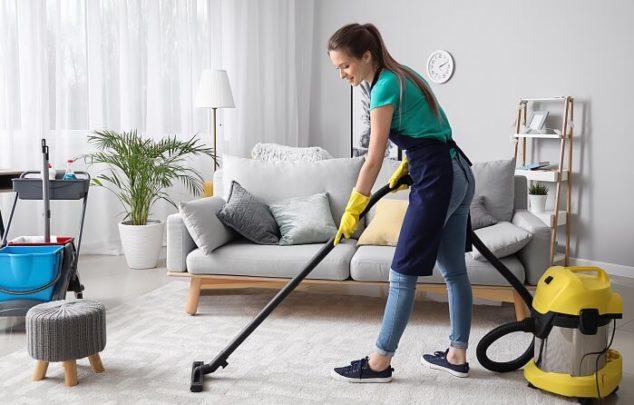 professional maid vacuuming a carpet